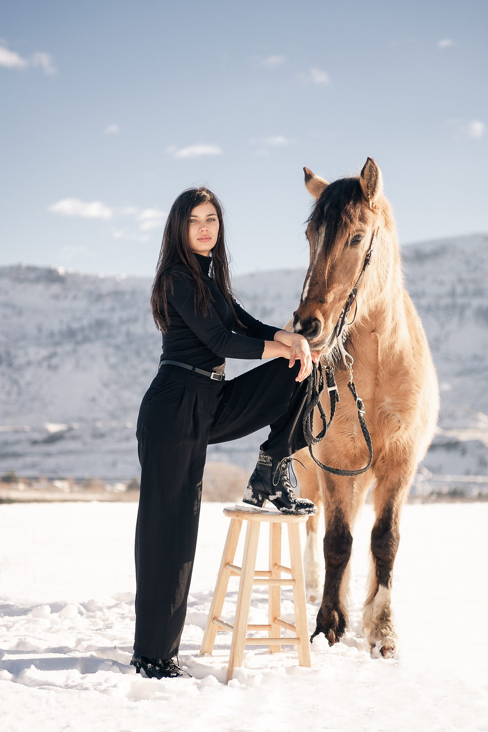 a girl wearing all black, with long dark hair, standing next to her buckskin mustang