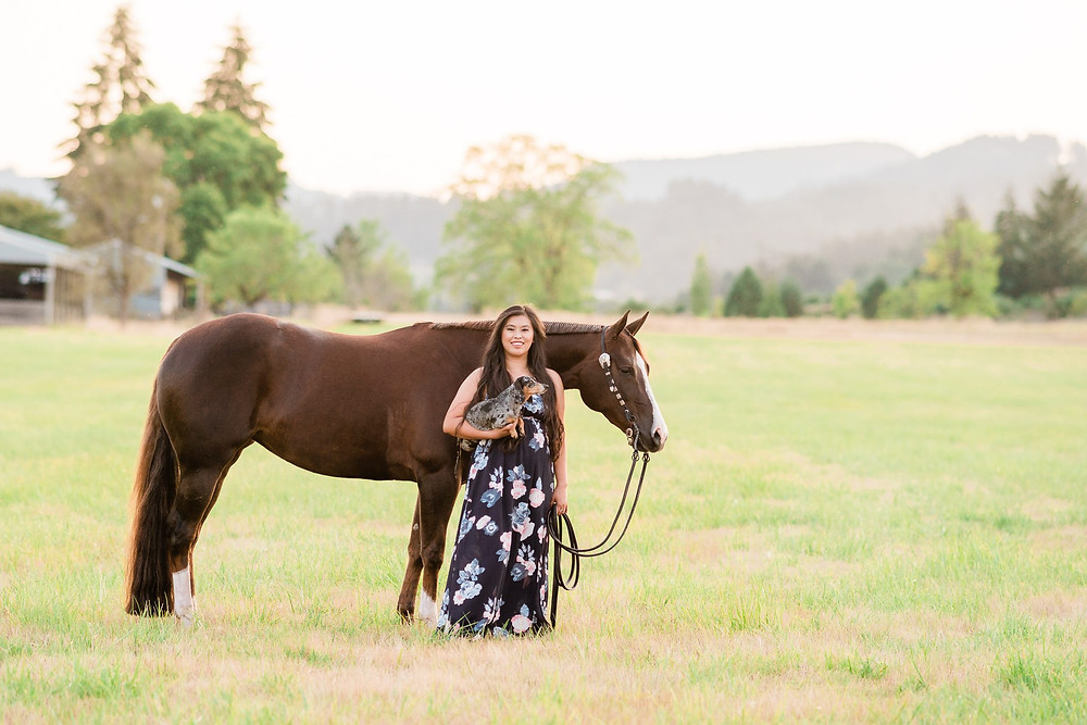 Chloe standing in a field with her chestnut quarter horse mare, Marion, and her dog, Lucy in McMinnville, OR