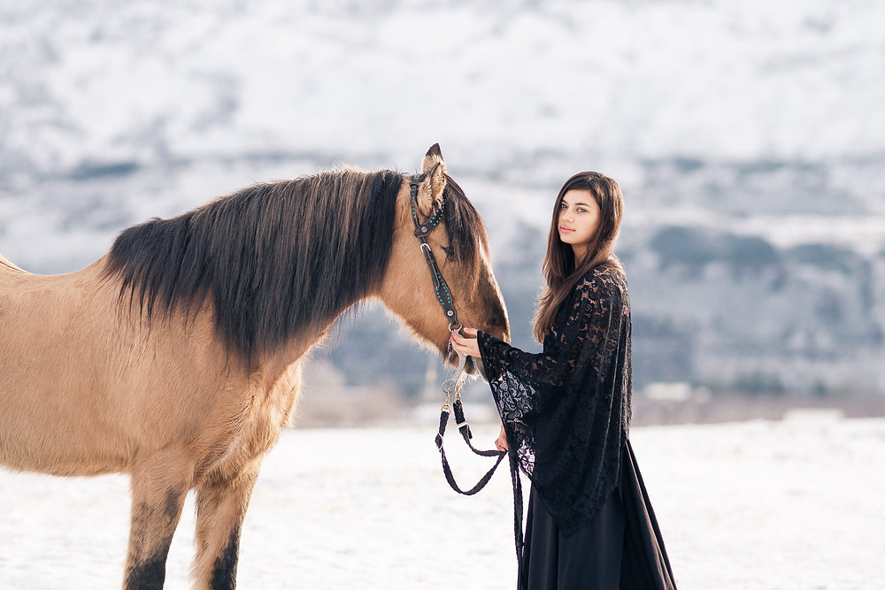 a girl wearing a long black dress standing in snow with a mountain in the background, petting her buckskin mustang horse