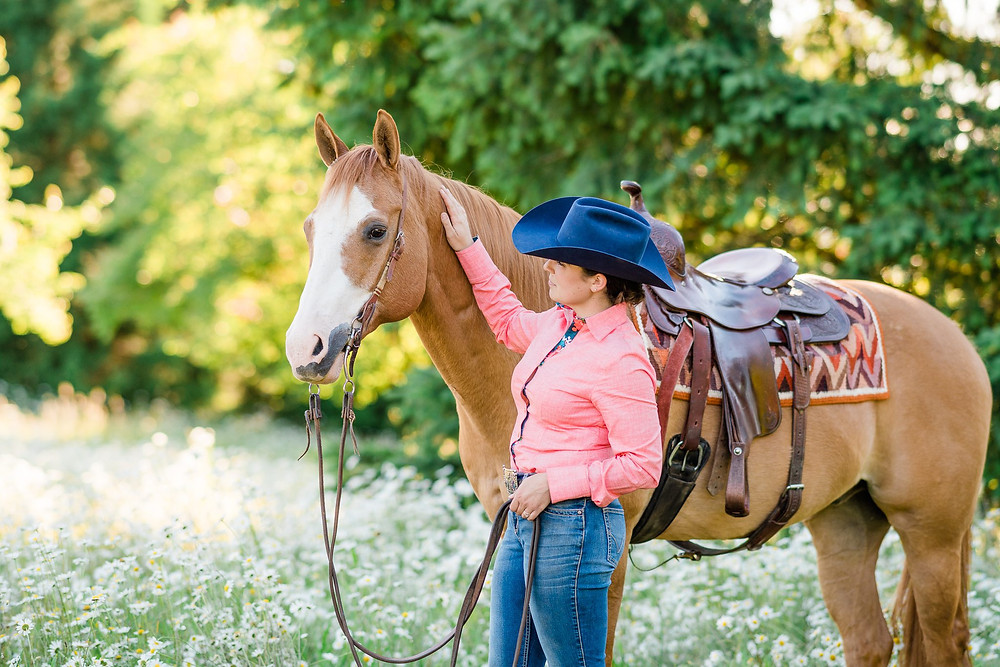 Katie petting Rico on the neck, while standing in a flower field wearing a blue Greely cowboy hat and a pink CR Ranchwear shirt