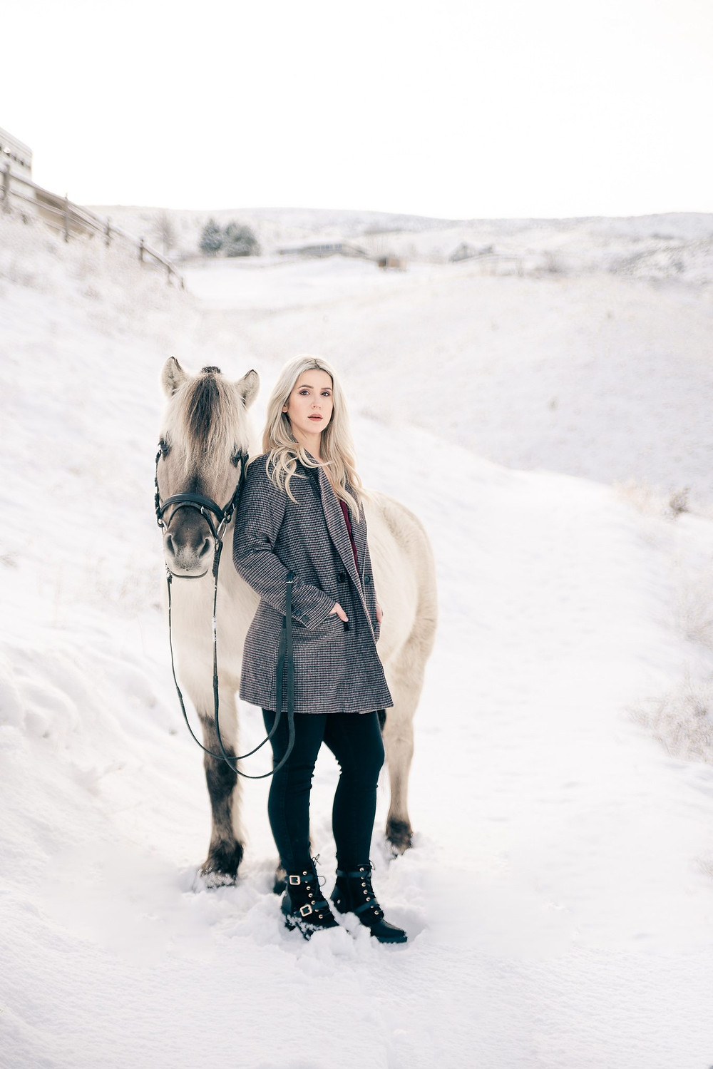 A blonde girl standing next to her Fjord horse in the snow in Wenatchee