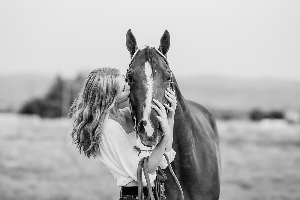 a black and white image of a girl kissing her horse on the cheek