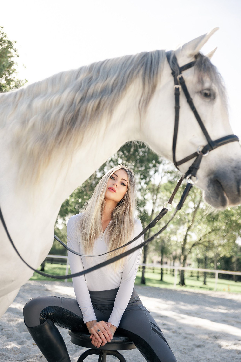 Alina sitting on a stool wearing English riding clothes, next to her horse, Santiago the andalusian in Wellington, Florida