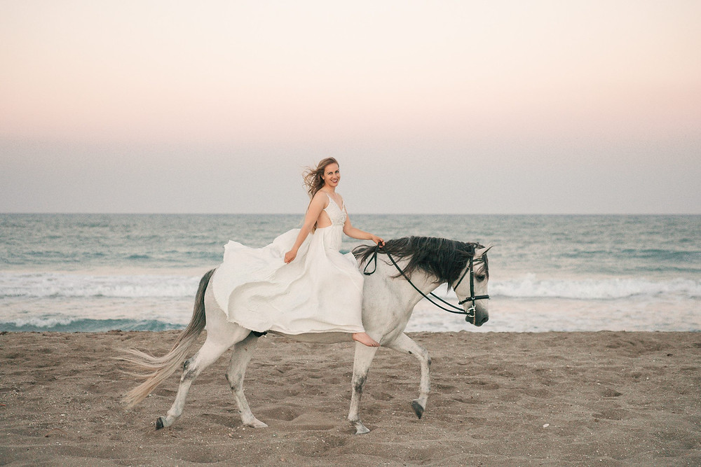 a blonde girl wearing a white dress sitting on her grey andalusian horse as they walk along the beach in Florida