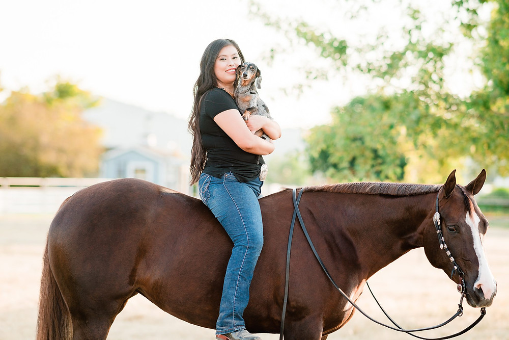 Chloe Teplick sitting on her chestnut mare, Marion, bareback while holding her dachshund dog