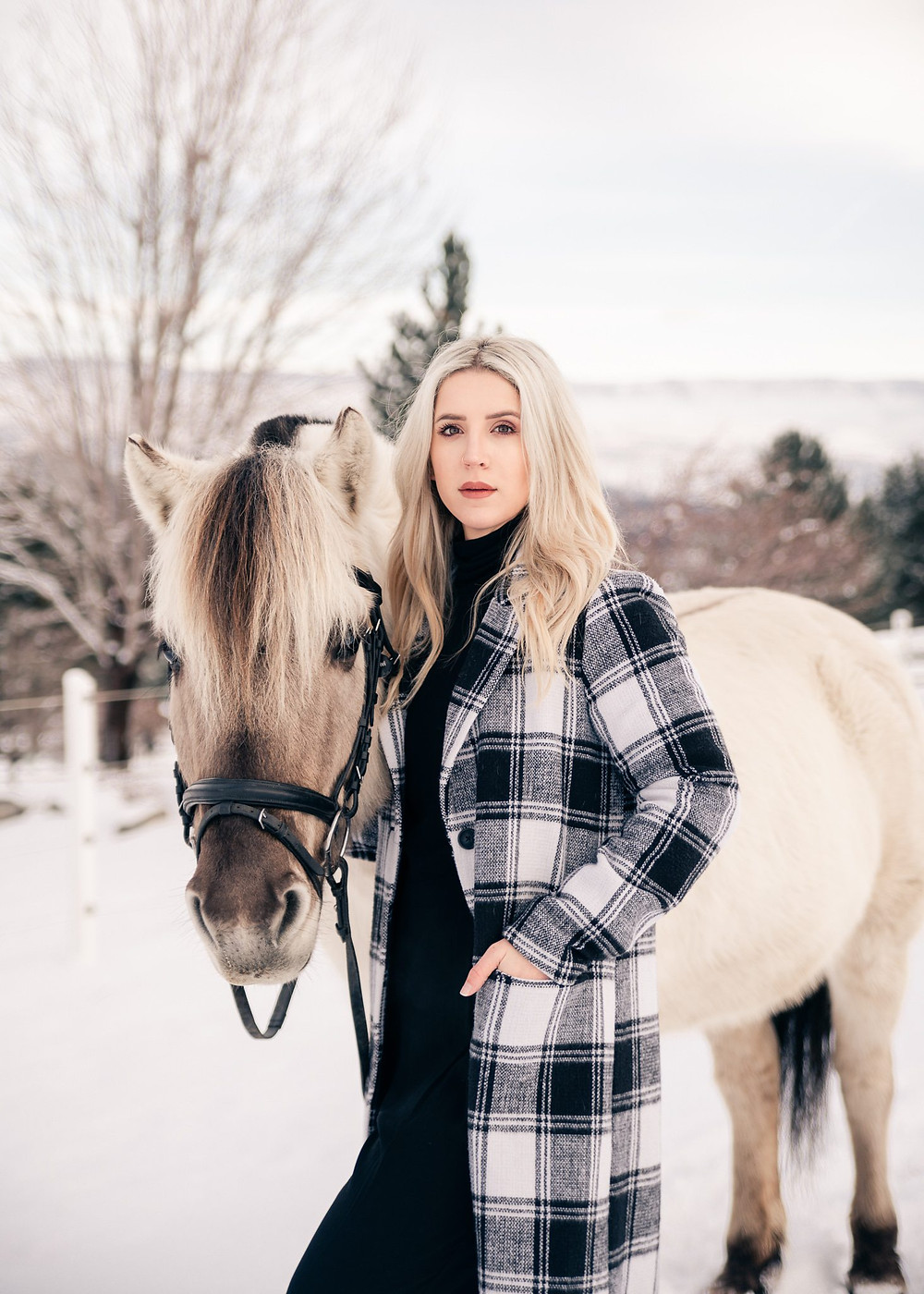 a girl standing next to her Fjord horse, with her hand in her coat pocket
