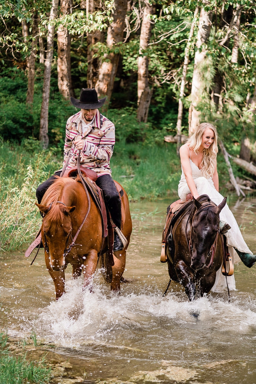 Cassy and Jake riding their horses through a pond in Rathdrum, Idaho