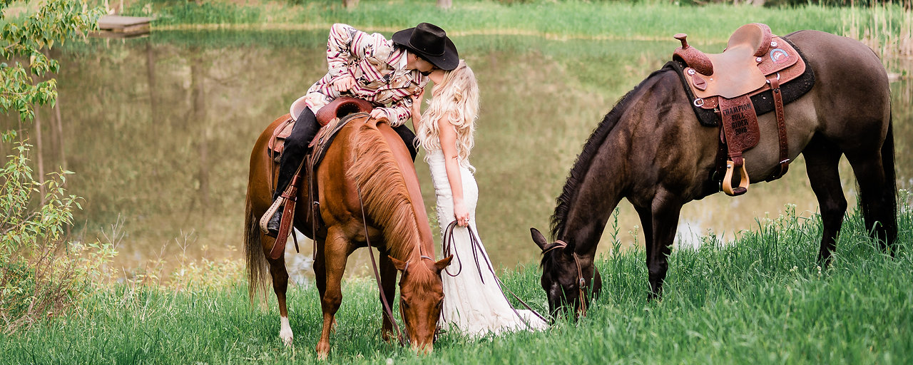 A husband and wife kissing on their wedding day, with their two horses