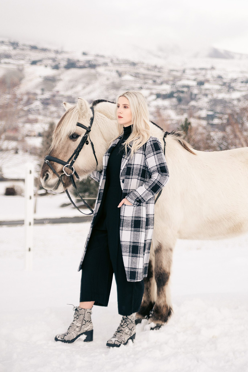 A girl standing next to her horse, looking off into the distance in the snow