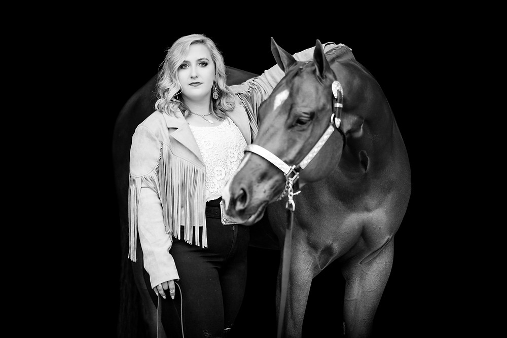 a black and white black background image of a girl wearing a fringe jacket with her horse looking into the camera
