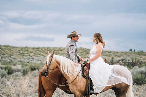 a newly wed sitting on their horses looking into their eyes, wearing their wedding tux and dress