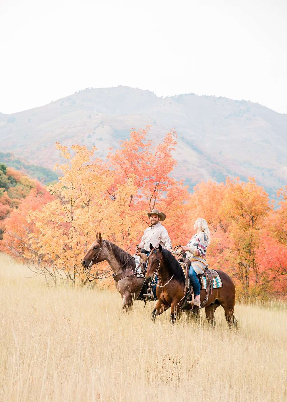 Lauren and Dj riding their horses through the valley with the beautiful fall colors