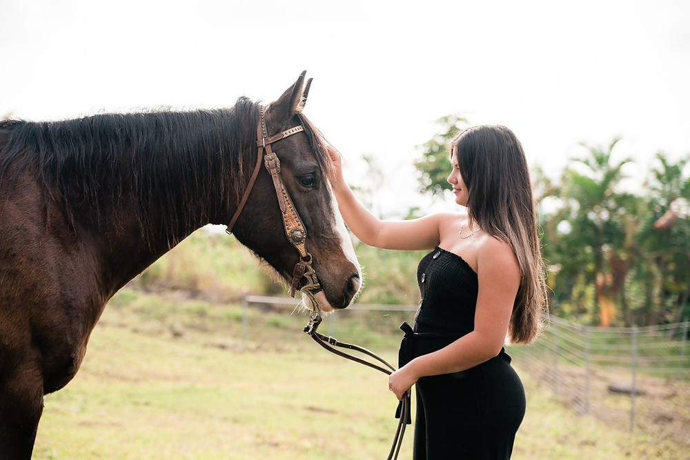 a Hawaiian girl dressed in a black strapless jumpsuit, petting her horse on his face- with palm trees in the background on the Big Island, Hawaii