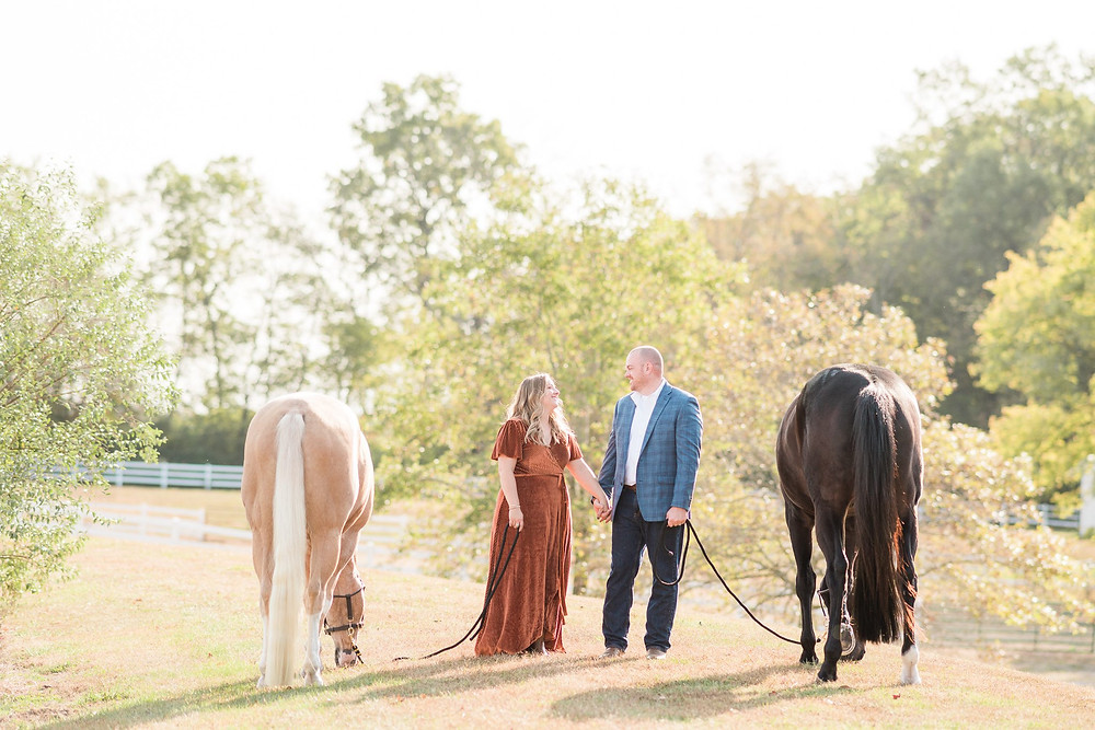 Amanda and Chris standing between Edward and Bailey holding hands, looking at each other with the horses graze