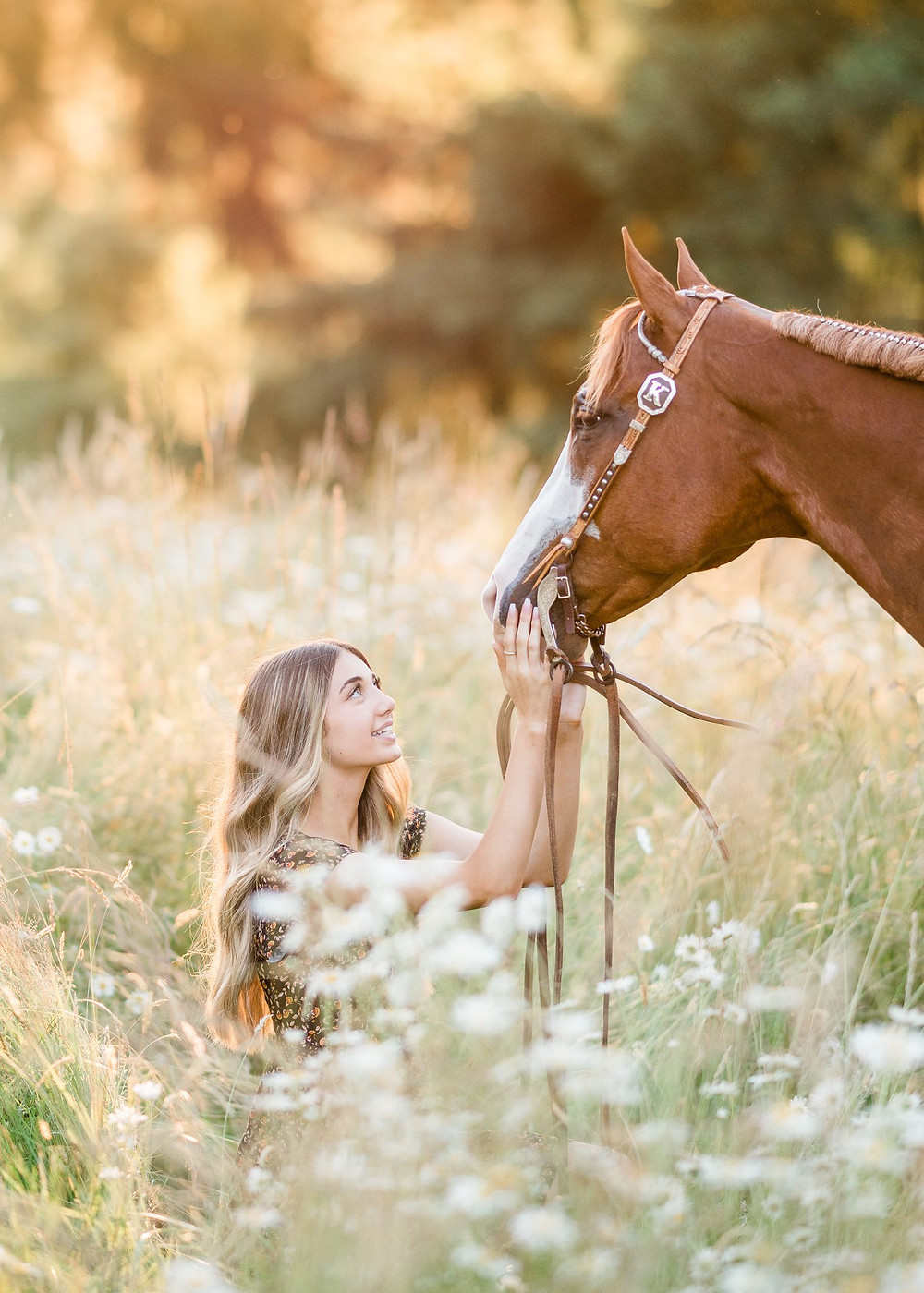 Kaitlyn sitting in a flower field looking up at her paint horse, Jimmy John