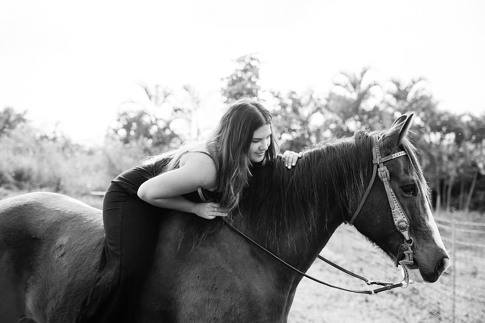 a girl laying on her horse's back looking at him smiling- in black and white