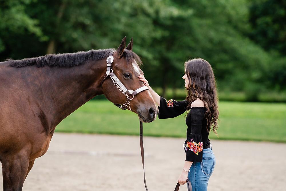 Jenna petting Bo, her bay AQHA horse on the head