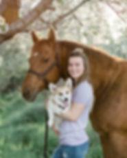 Jeni Jo Photography holding her corgi standing next to her sorrel mare