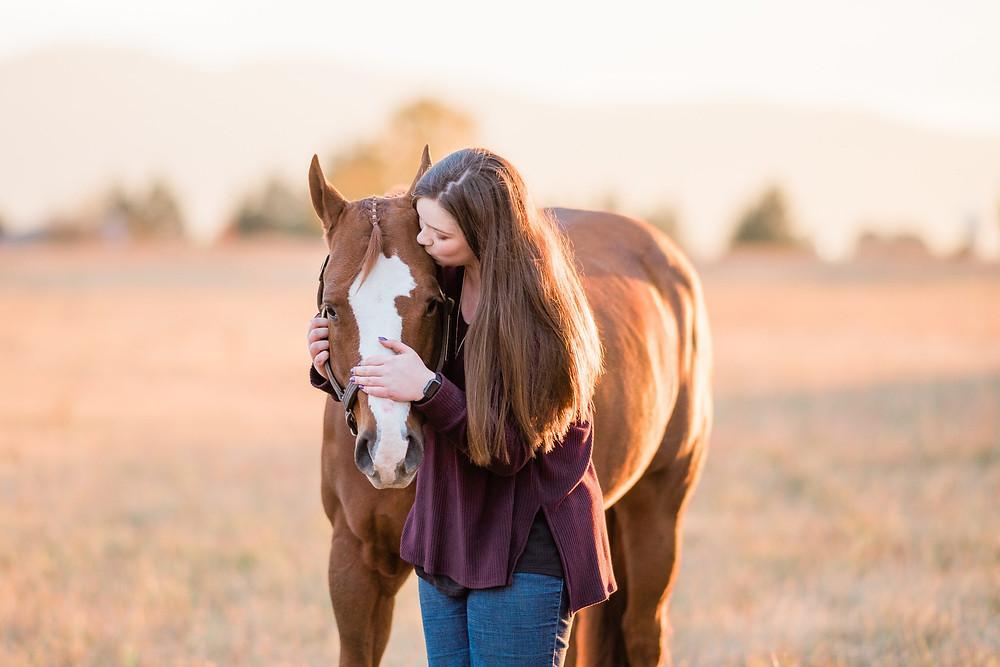 Hailey Schmidt kidding her sorrel quarter horse gelding on the top of his head
