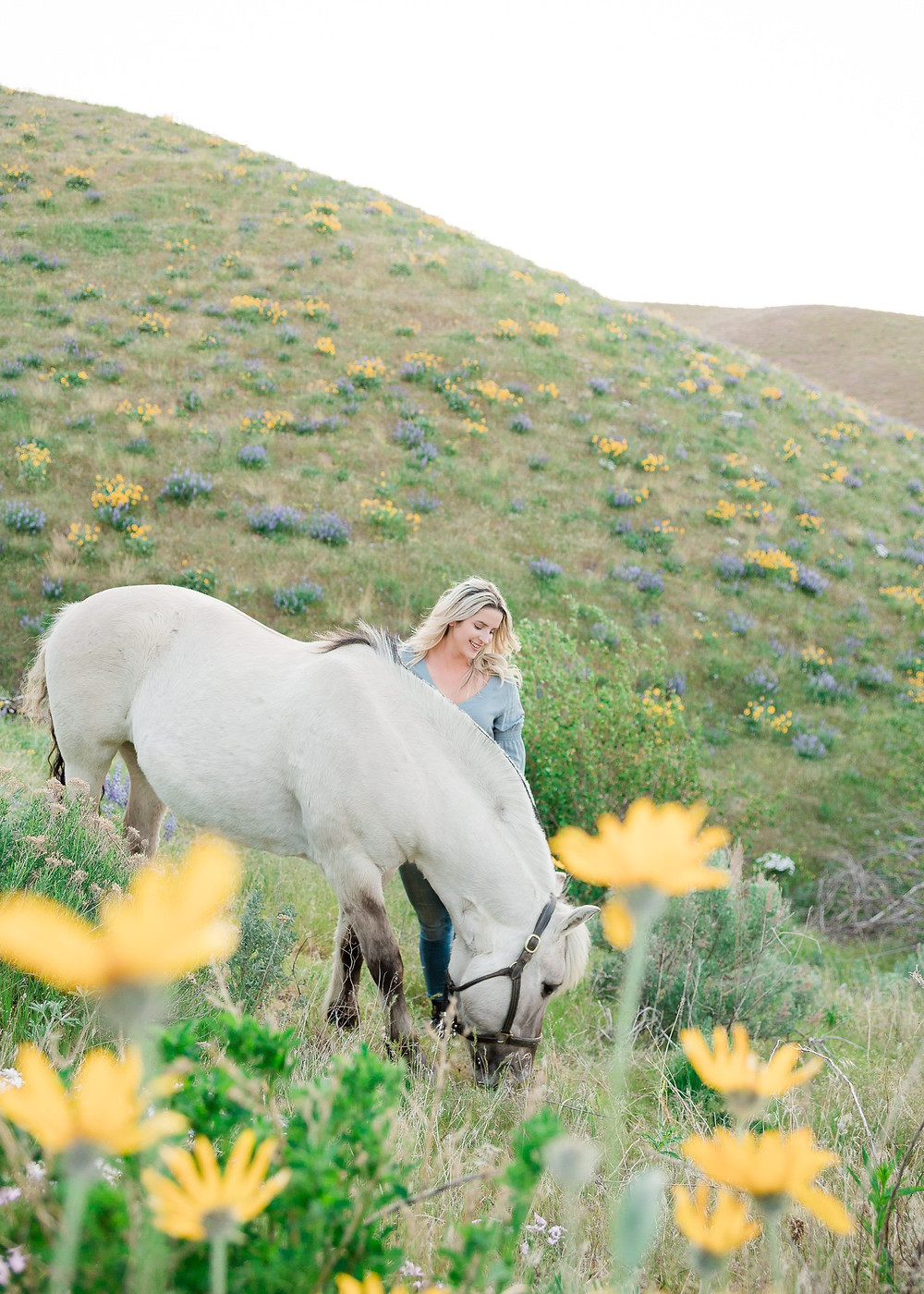 Ashley standing next to Solvi, her fjord mare, while she grazing in the green grass & wildflowers