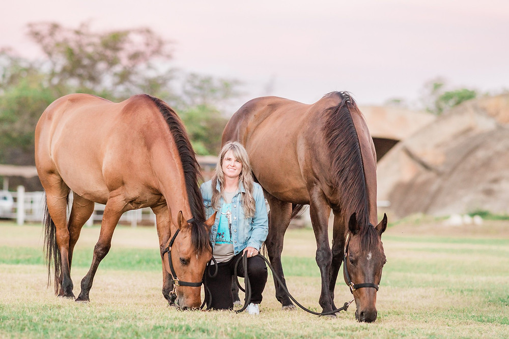 Lindsey Vandolah kneeling down with her two horses, Rocky and Tucker, grazing in the green grass at Barber's Point Stables in Kapolei, HI