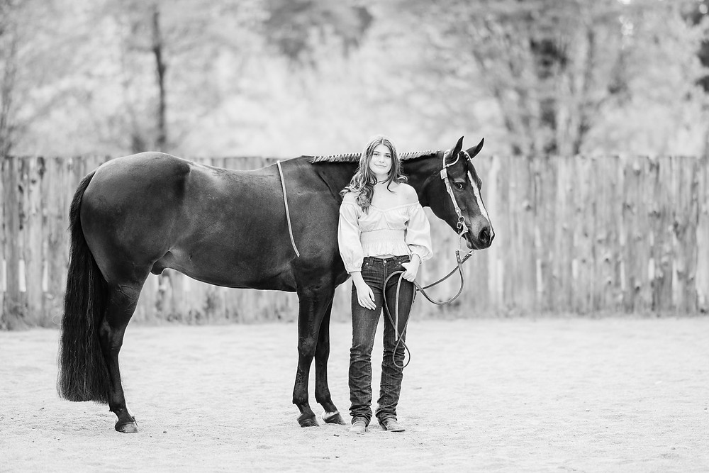 a black and white image of a girl standing next to her bay AQHA gelding in Lake Stevens, WA