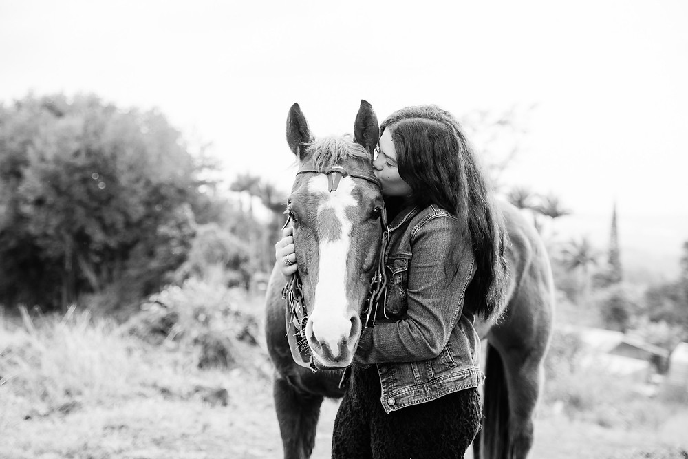 a girl hugging and kissing her horse on his face, in black and white