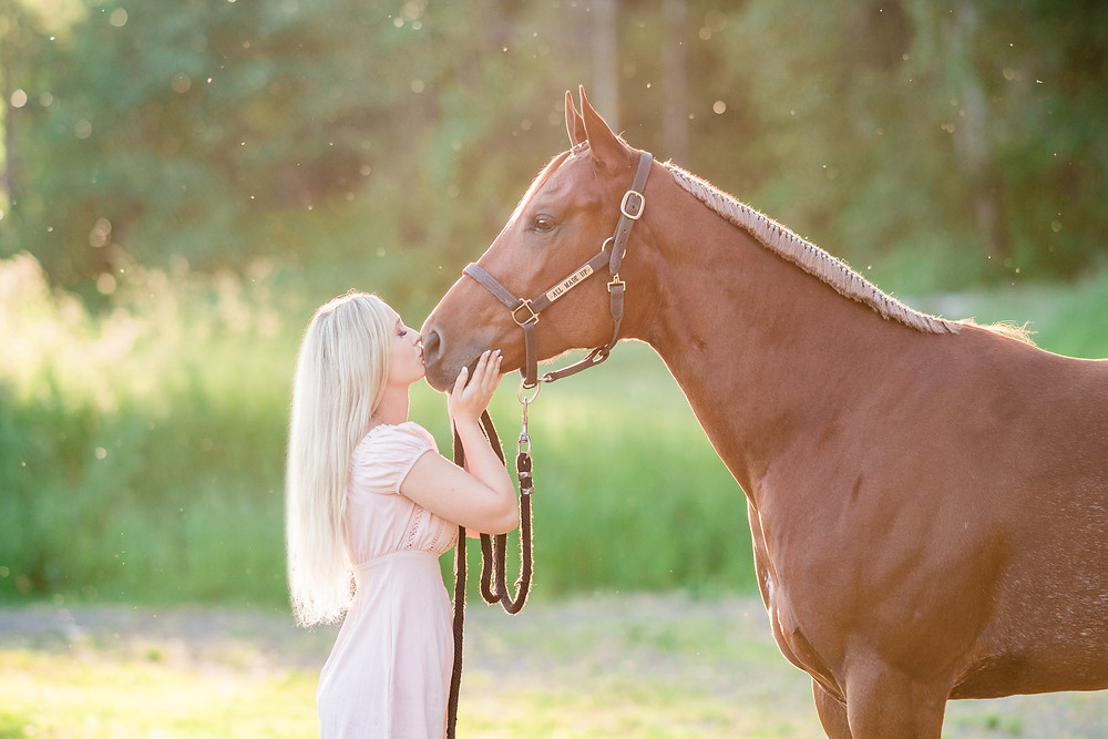 Caitlin kissing Ava, her AQHA sorrel mare, on the nose