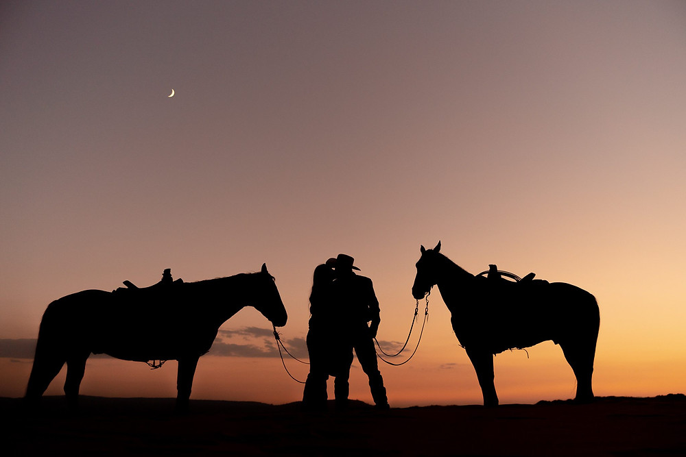 Silhouette of Josie and Brody with their two horses, B Cross and Dagger