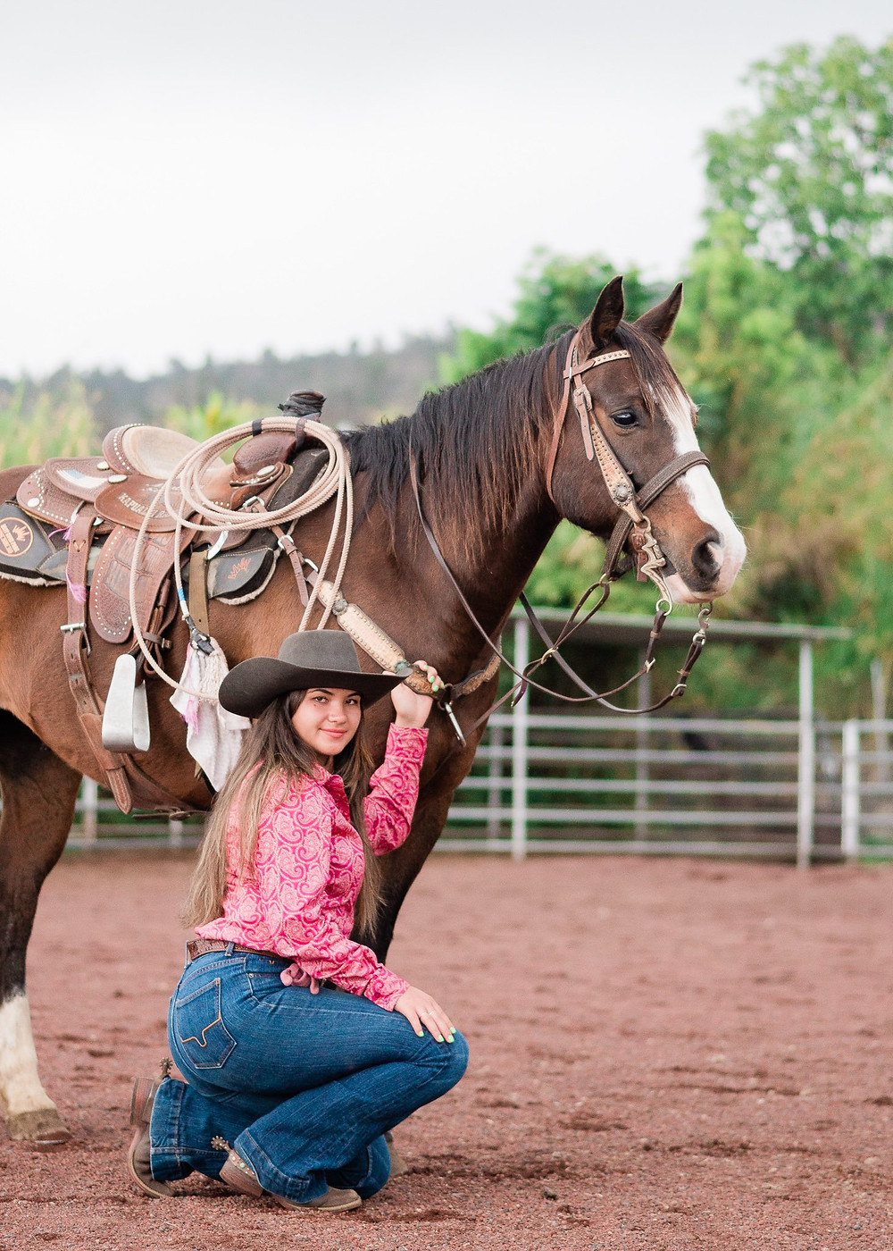 a Hawaiian girl with long dark hair, wearing a pink shirt and Kimes jeans, kneeling next to her horse