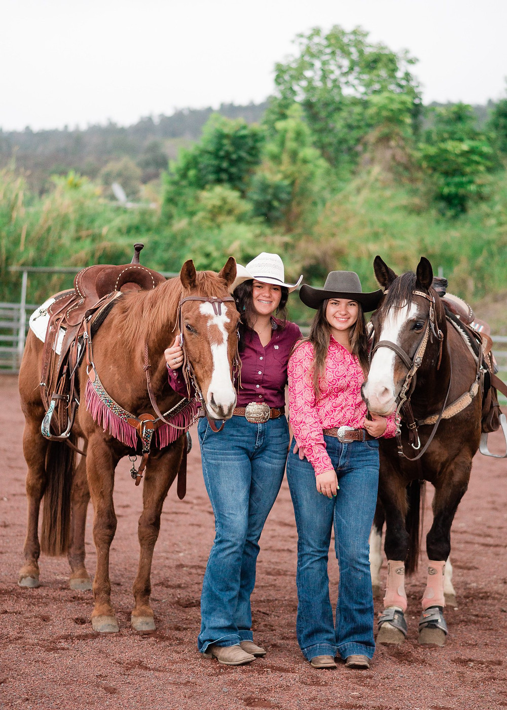 two sisters dressed in rodeo attire, standing next to their horses smiling at the camera