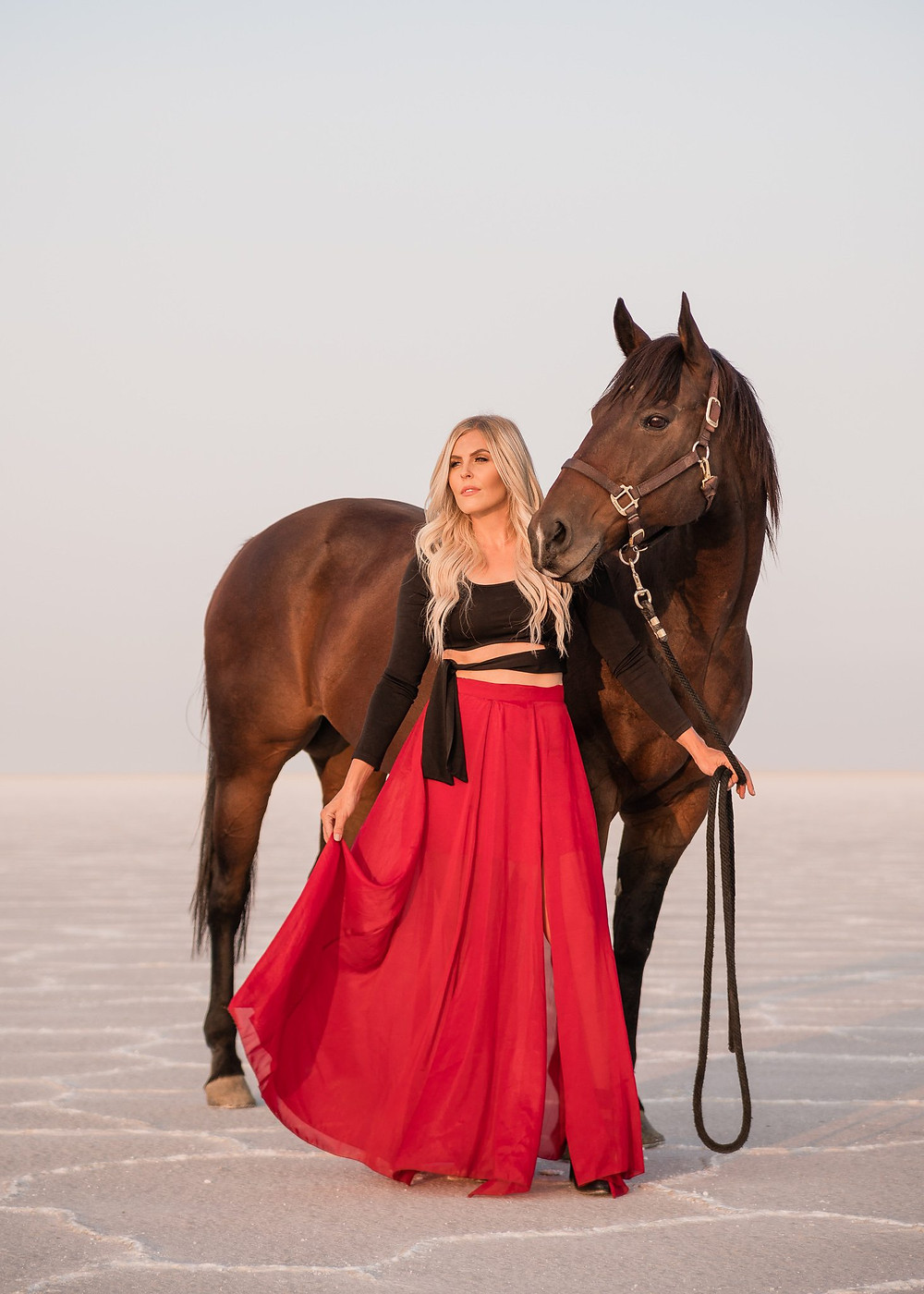 Davie wearing a red skirt flowing in the wind at the Bonneville Salt Flats, with her bay quarter horse gelding, Dry