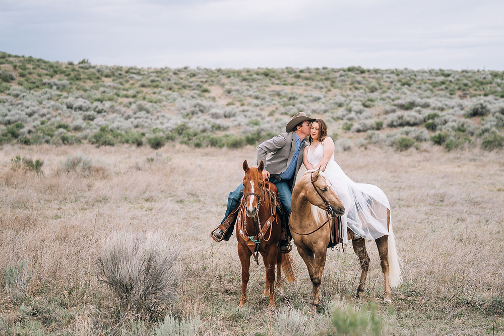 a groom kissing his bride on the cheek on their wedding day in the desert of Washington