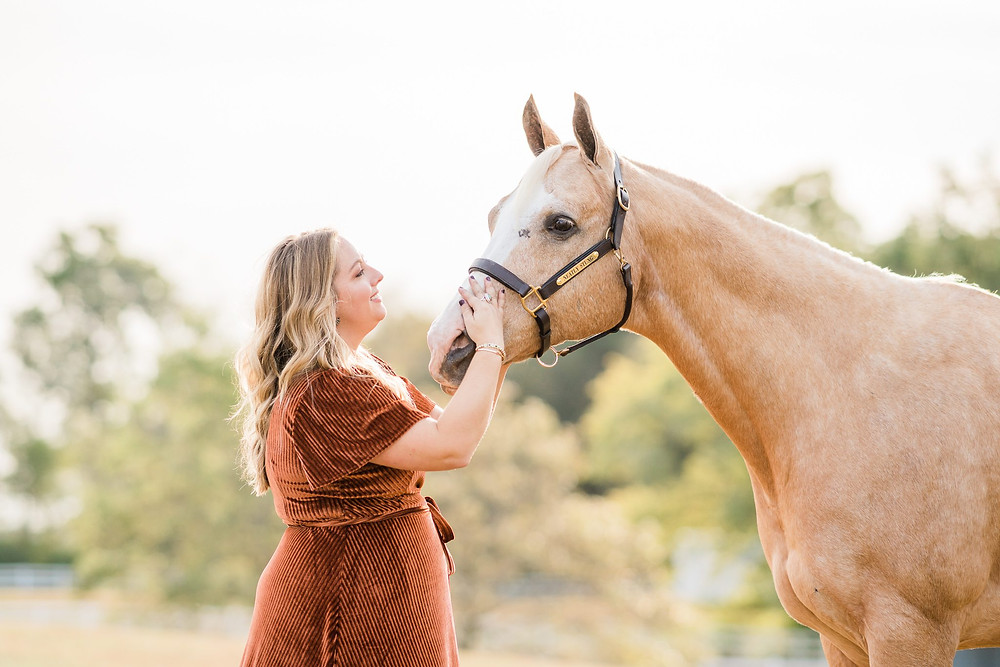 Amanda petting Bailey, her palomino quarter horse gelding, on the nose, smiling up at him