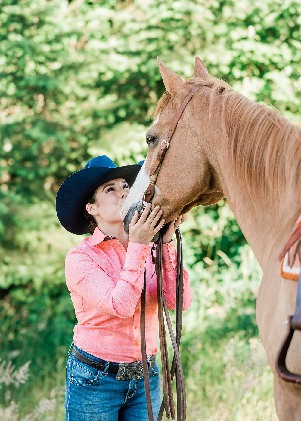 Katie kissing Rico, a red Dun quarter horse on the nose