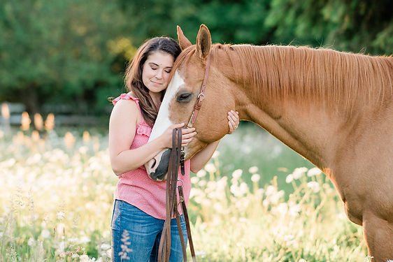A girl hugging her horse's face, with her eyes closed