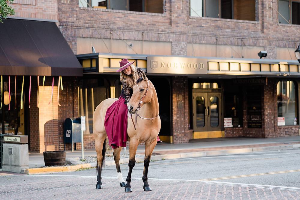 Breanna Howell riding Legs through downtown Wenatchee on Wenatchee Avenue, near the Morrison Building