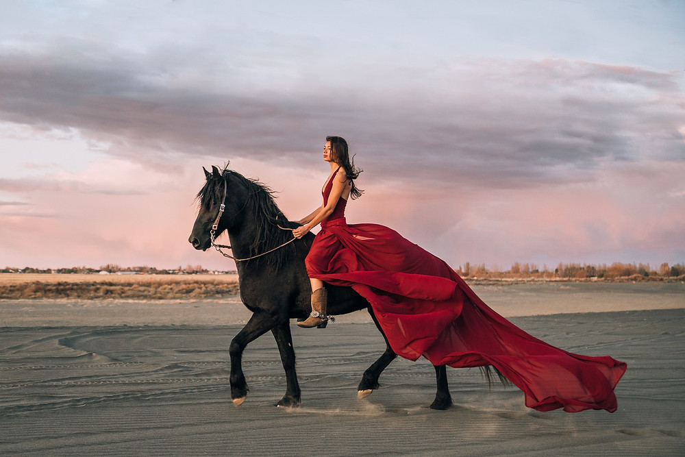 Soli riding Samson with a long maroon dress in the desert