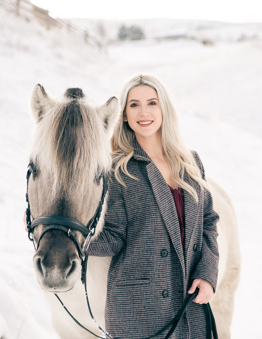 a blonde girl standing next to her Fjord horse, wearing a grey coat in the snow