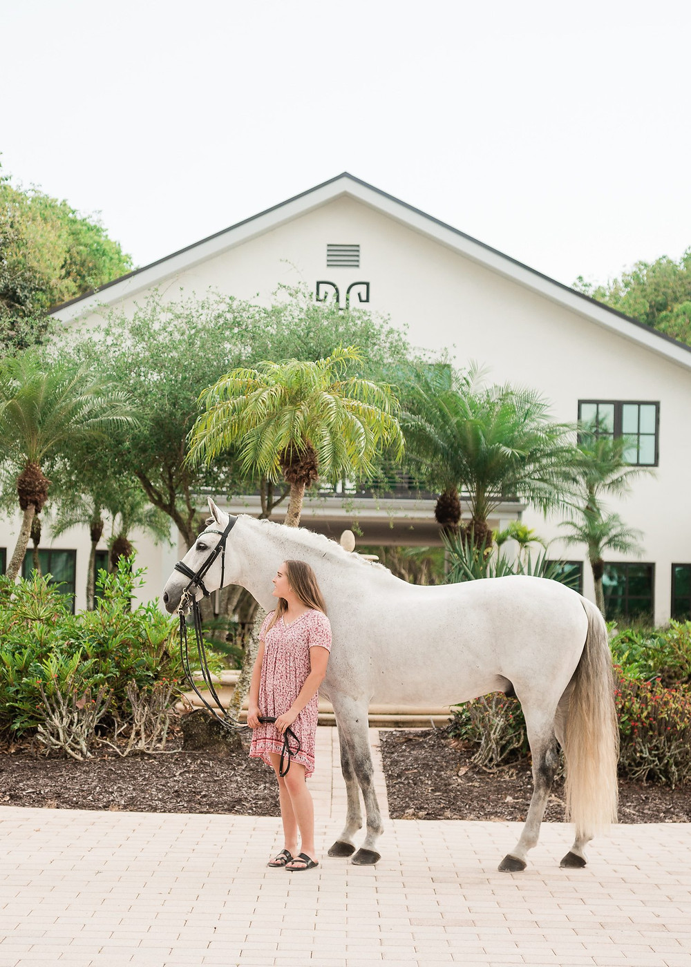 Working student, Jordan Lockwood, standing in front of Helgstrand Dressage barn at Windsome Farms in Wellington, FL with her grey Andalusian stallion