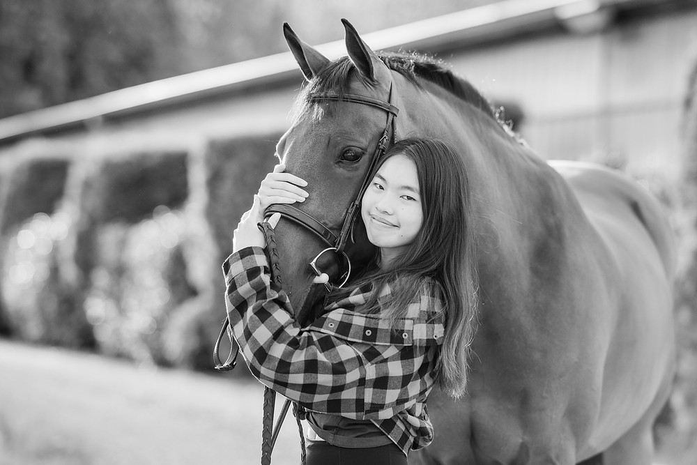a black and white image of Kristen hugging Cass, her gelding's, face