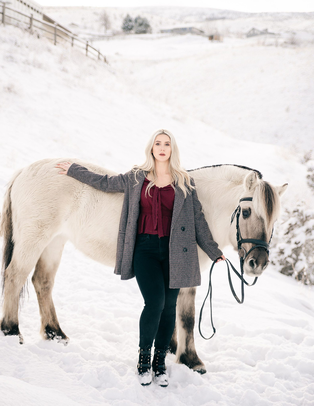A blonde girl wearing a maroon shirt, grey coat, and black pants, leaning up against her Fjord horse in the snow