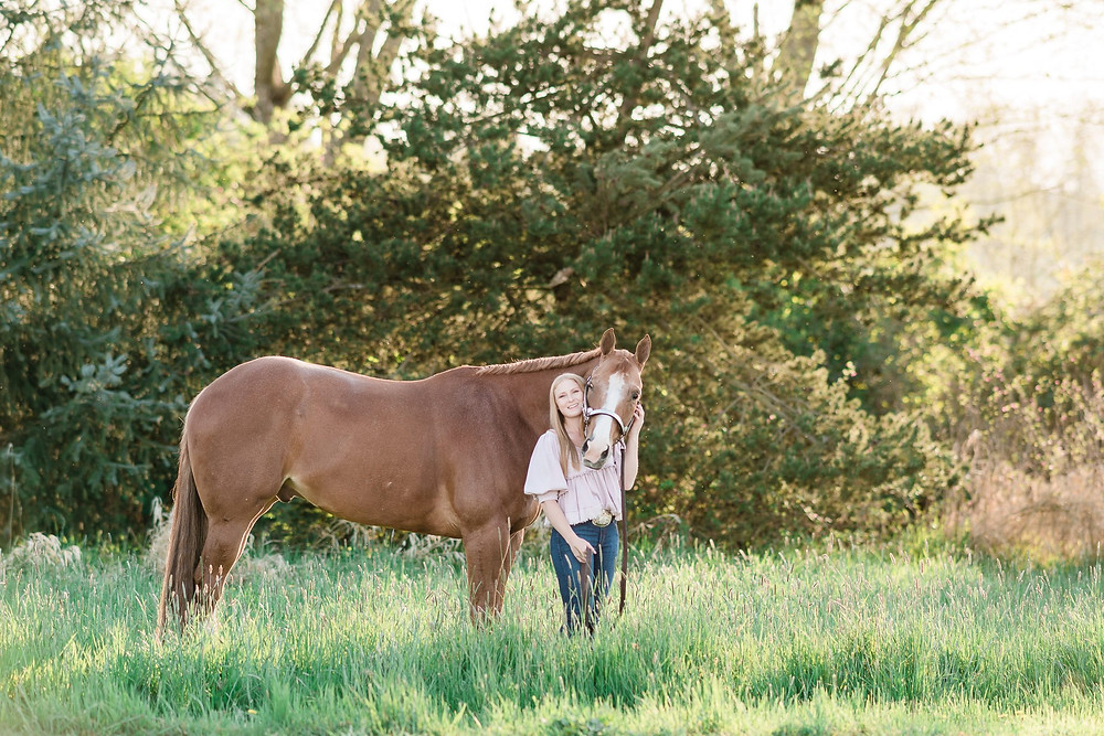 Ansley standing next to Leo by the outdoor arena at Lucky 13 Ranch in Arlington, WA