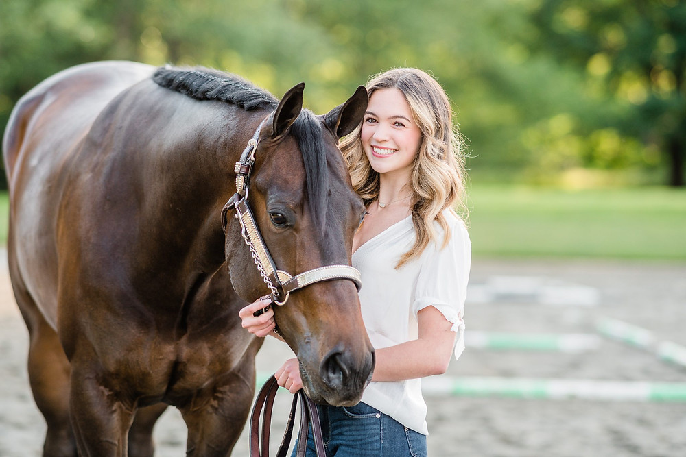 a headshot of a blonde girl smiling with her dark bay AQHA gelding