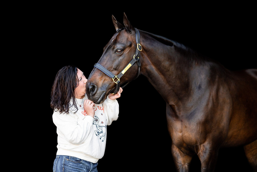 a black background image of Anne kissing Bentley on the nose