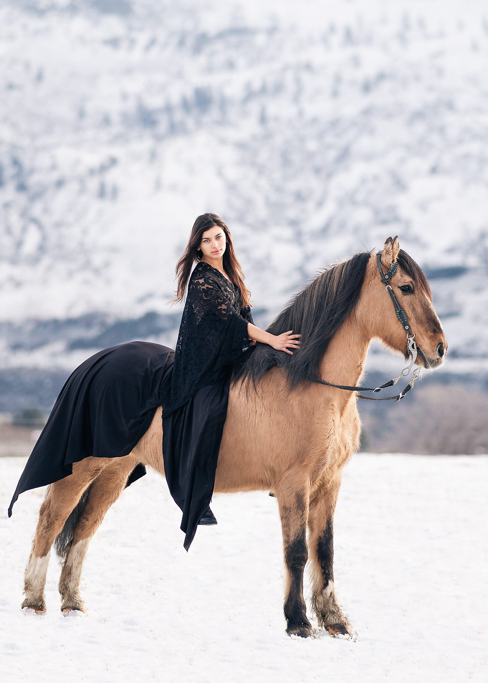a girl wearing a long black dress standing in snow with a mountain in the background, sitting on her buckskin mustang horse