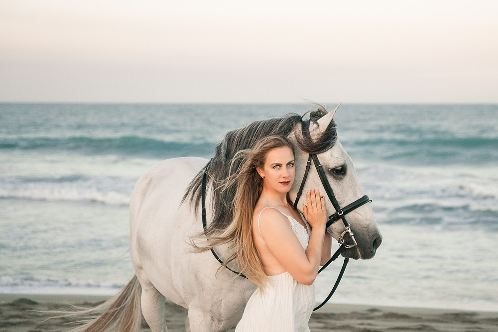 a portrait of a blonde girl wearing a white dress standing next to her grey andalusian gelding on the beach in Florida