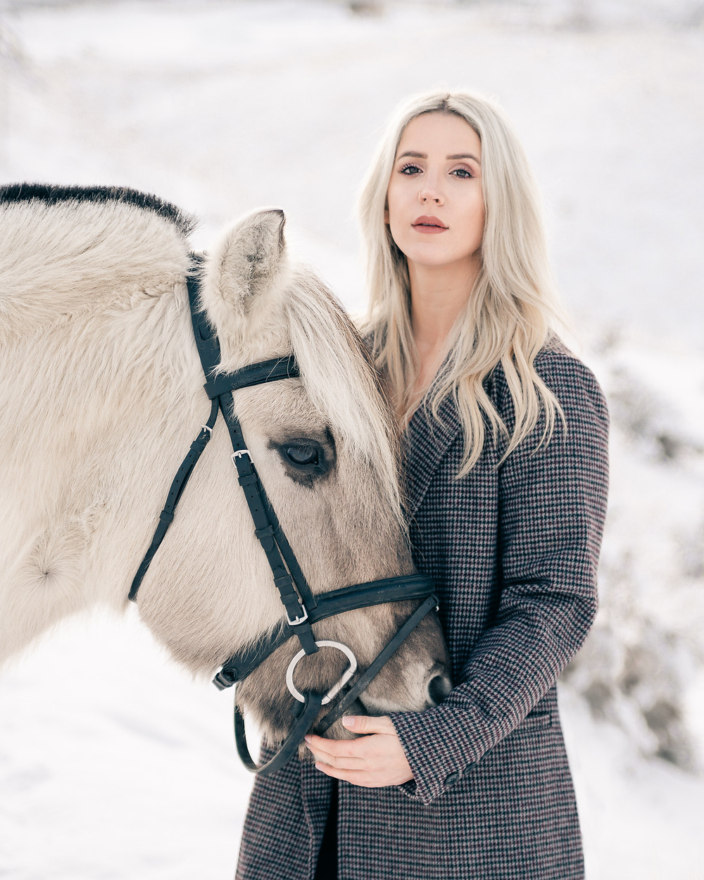A blonde girl hugging her horse's head, on a winter day in Wenatchee, WA