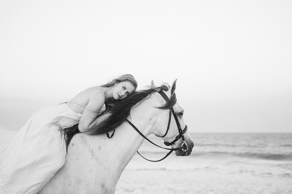 a black and white image of a girl laying on her horse's neck, at the beach in florida