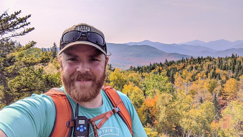 Selfie of bearded man on mountain top in fall.